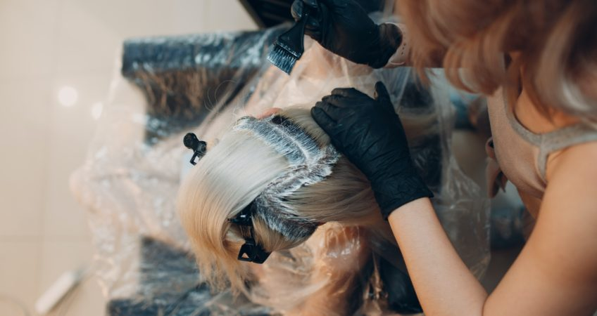 Blonde haired woman in a salon getting dark roots bleached by a stylist with black gloves